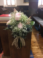 rustic looking pew ends tied in string  pink roses blue thistle