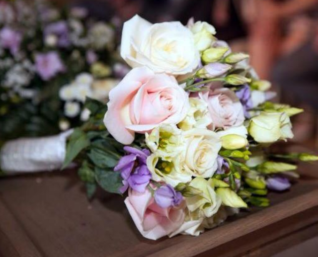 bridal bouquet hand tied roses with lilac lisianthus and freesia and foliages