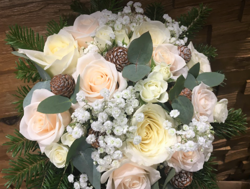 bridal bouquet hand tied touches of gypsophila and roses with cones and foliages