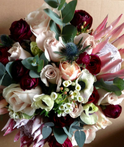 burgundy pinks & blue thistle wild looking bridal bouquet in the countryside