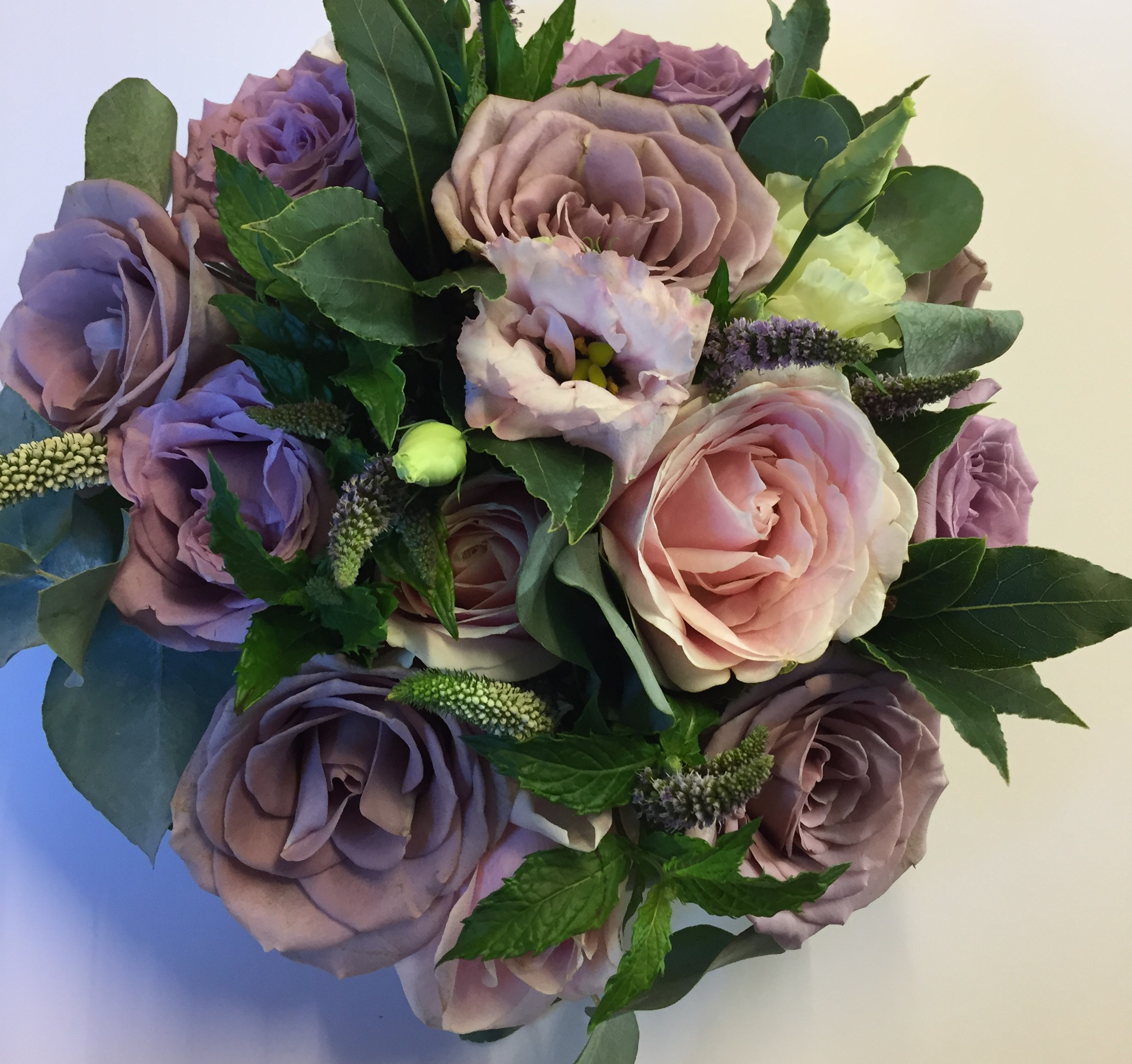 wedding flowers for bride in a hand tied style just roses lisianthus mint and bay leaves