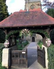 sprays of pink flowers soft ruscus large spray over arch Church gate arch entrance