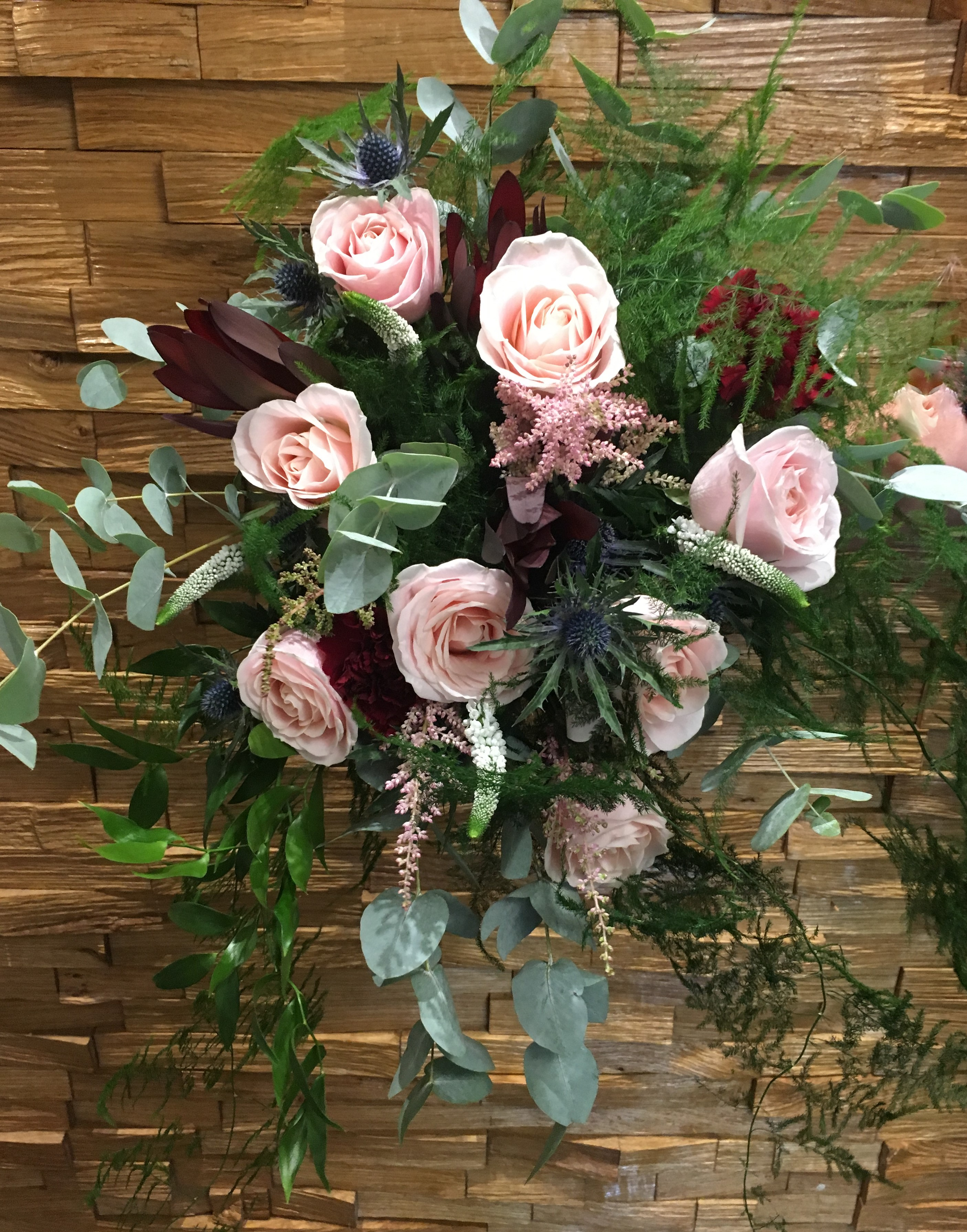 hand tied of roses thistle and lisianthus  freesia and veronica wild style