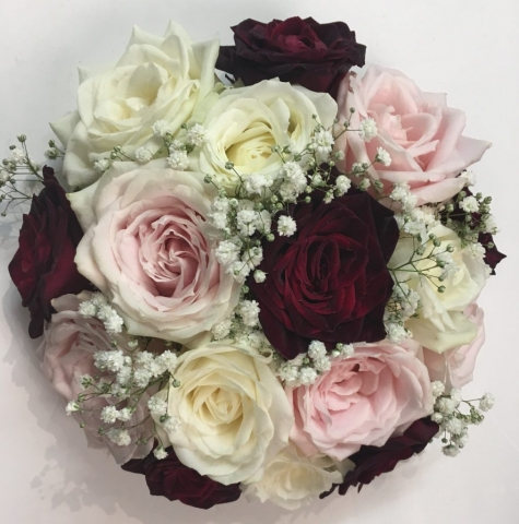 pastel and deep burgundy  flowers in bouquet white roses and pale pink hand tied bouquet