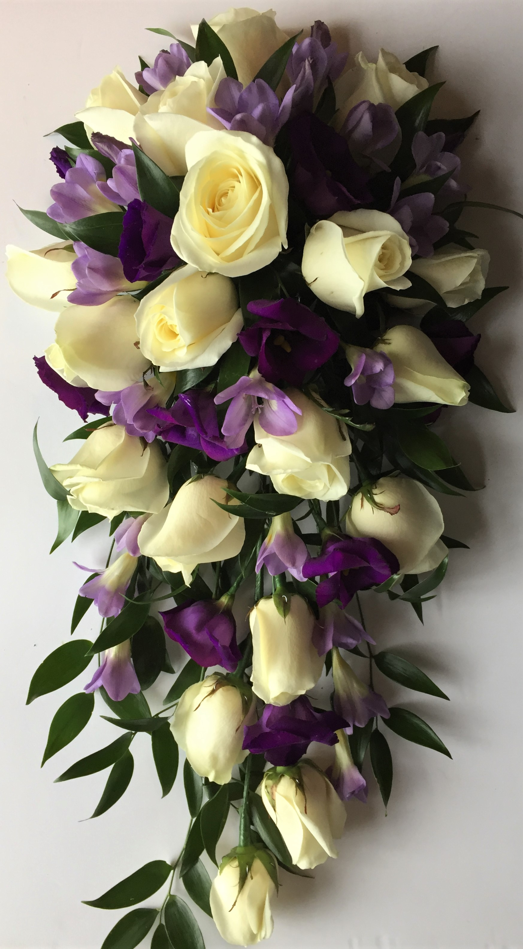 bridal flowers in a shower bouquet loose style of mint veronica and foliage lilac roses with ivory roses and purple lisianthus  cascading wedding bouquet florist in studley flair with flowers