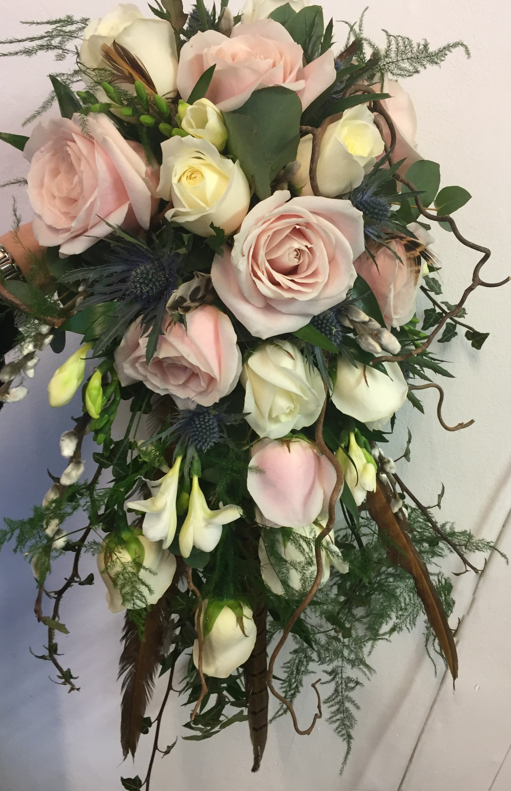 rustic wild theme wedding cascading shower  bouquet of roses and foliages