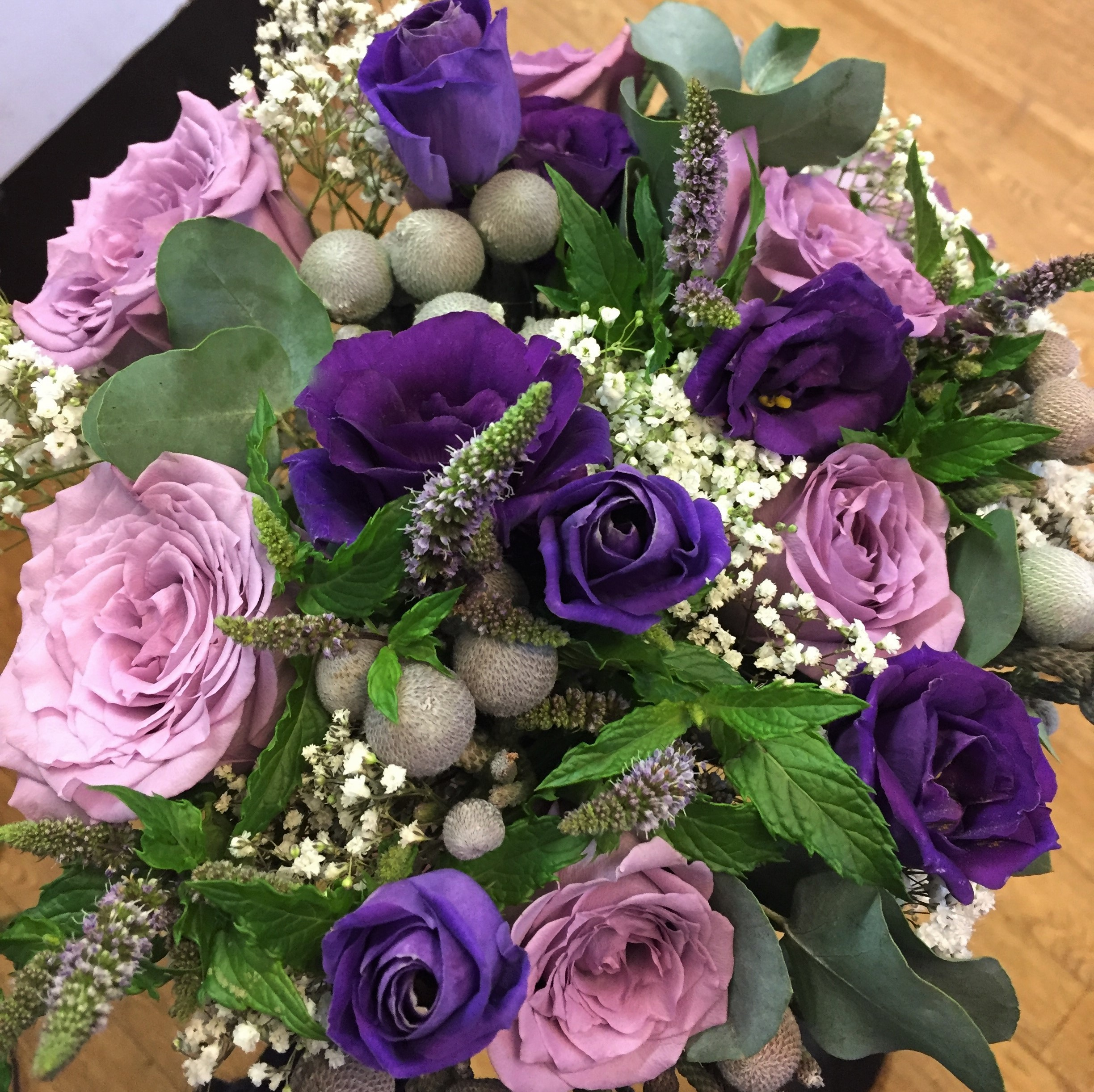 bridal flowers in a hand tied bouquet loose style of mint veronica and foliage lilac roses with ivory roses and purple lisianthus  hand tied wedding bouquet florist in studley flair with flowers
