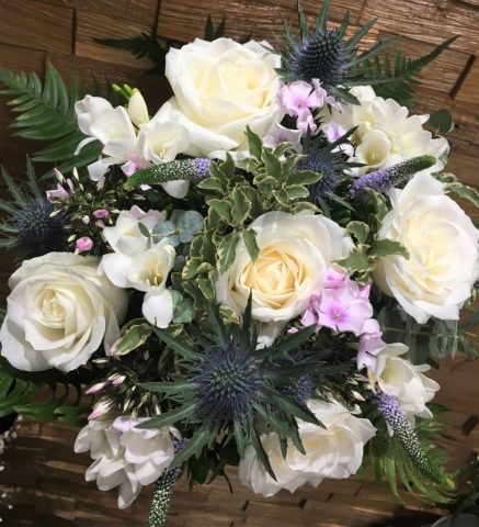 hand tied of roses thistle and lisianthus  freesia and veronica
