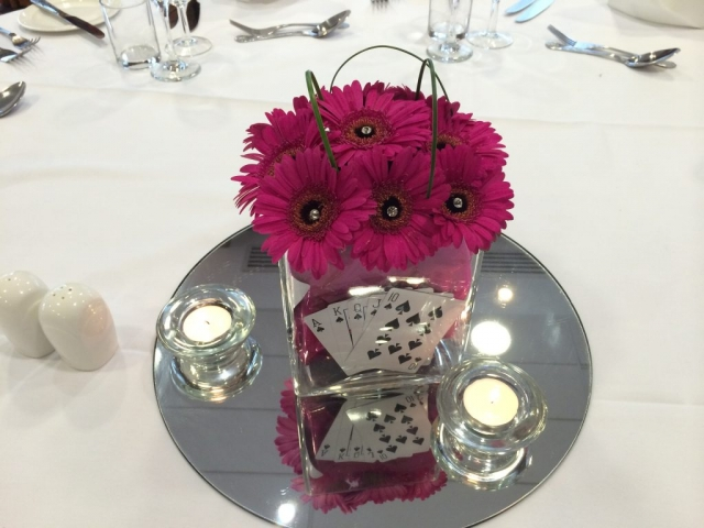 something different Poker theme arrangements cerise pink cube table arrangement abbey hotel