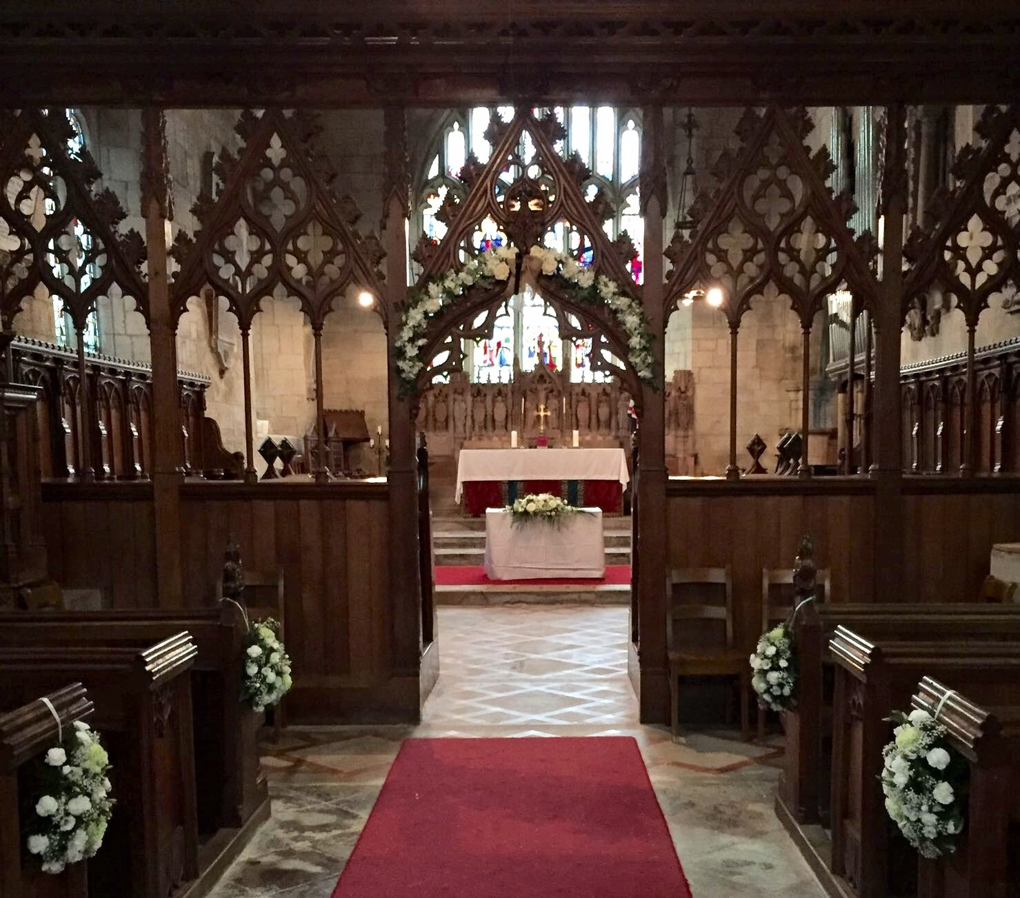 church dressing arch flowers alter arrangements pew ends white flowers Wroxall Abbey aisle arch with alter arrangement