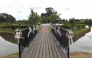 pink & white pew end & bows over bridge ardencote manor