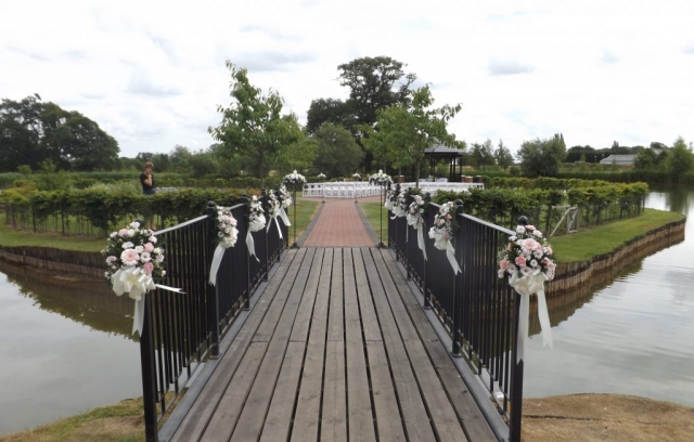 pink & white pew end & bows over bridge ardencote manor