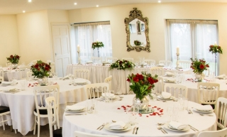 Reception flowers of red rose and christmas foliages in goldfish bowls bordesley park
