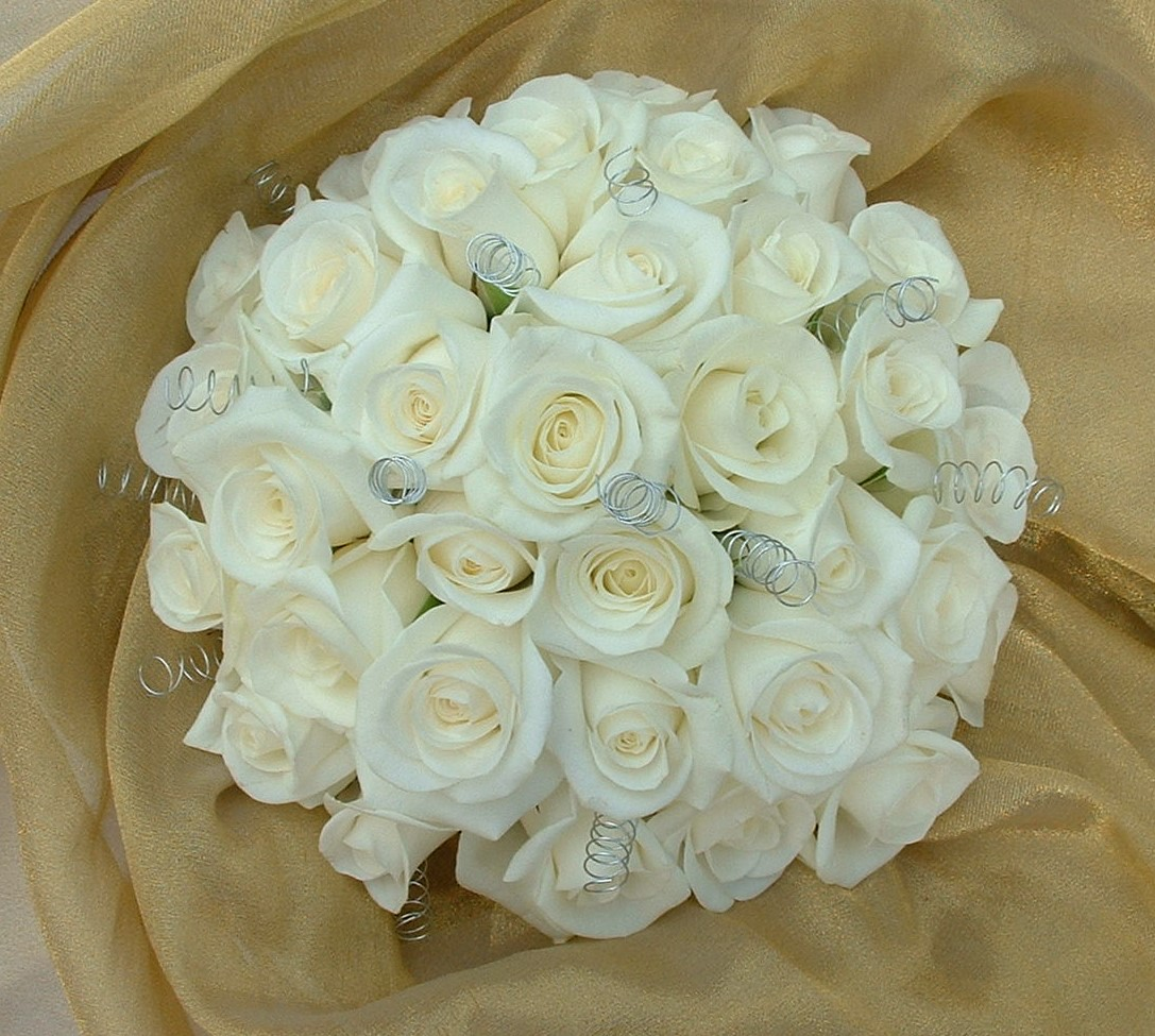 wedding flowers for bride in a hand tied style just ivory  roses