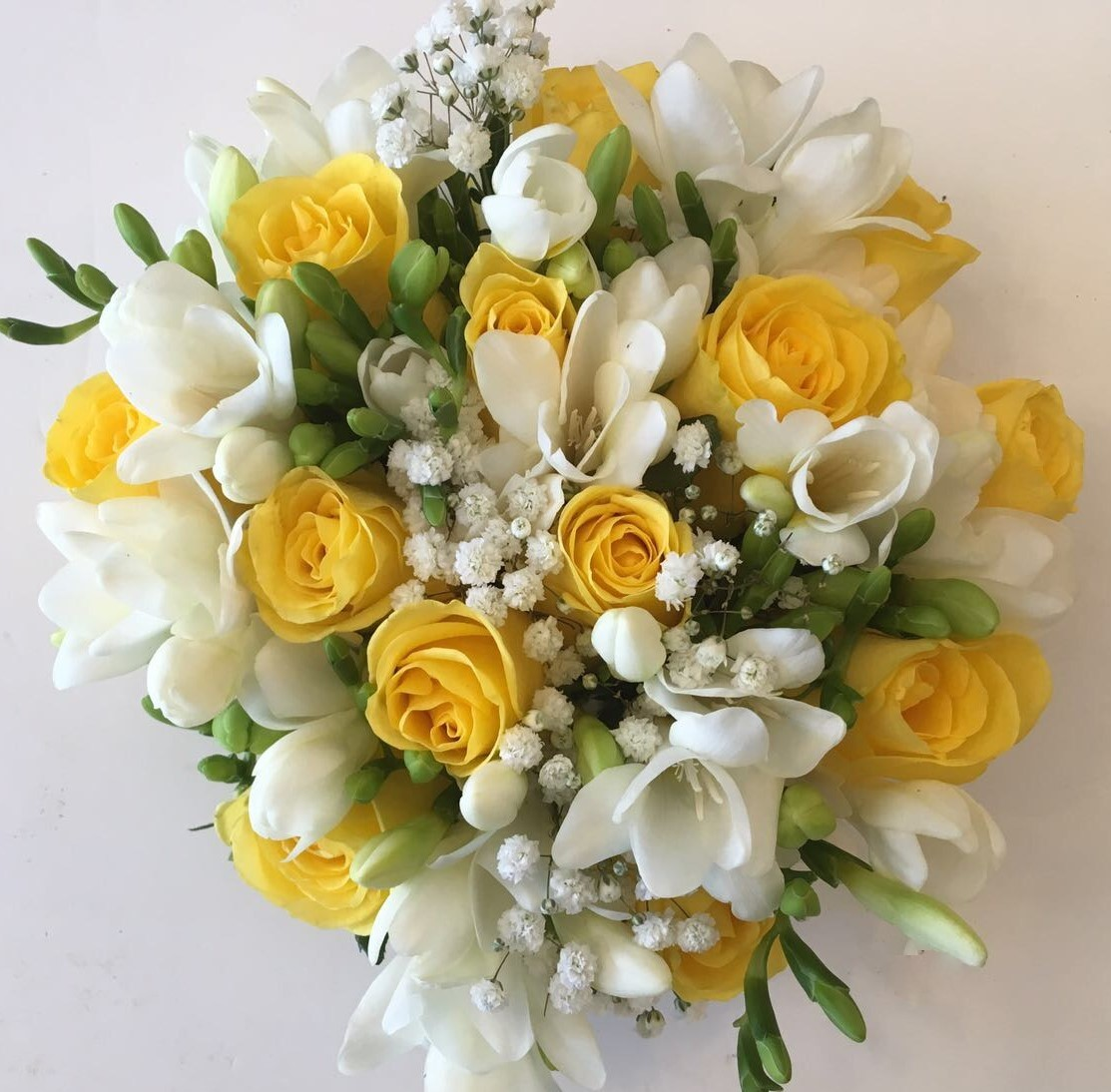 bridal bouquet hand tied touches of gypsophila and yellow roses with freesia