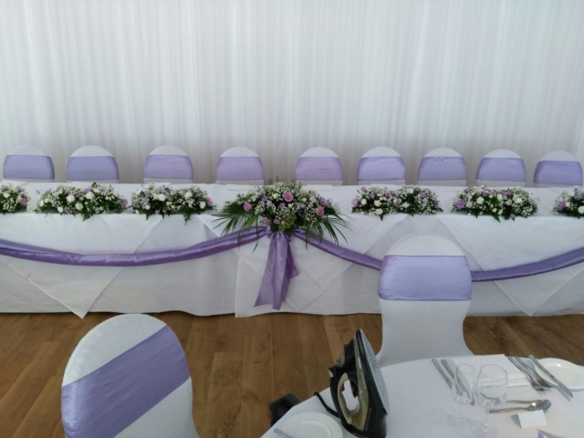 Top table with lilac swags and flowers