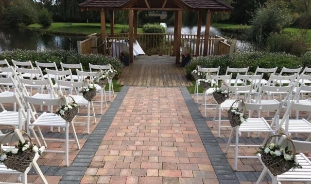 white flower wicker baskets down aisle  Outside weddings Wootton  Park white flower wicker baskets down aisle