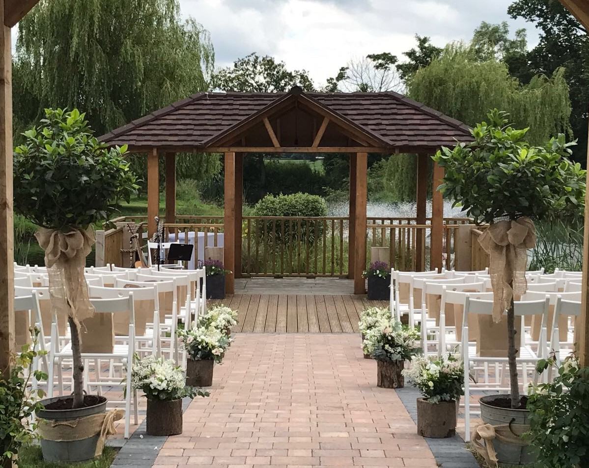 wooton park bay trees down aislewooton park bay trees Outside weddings  white flower rustic log trunks down aisle