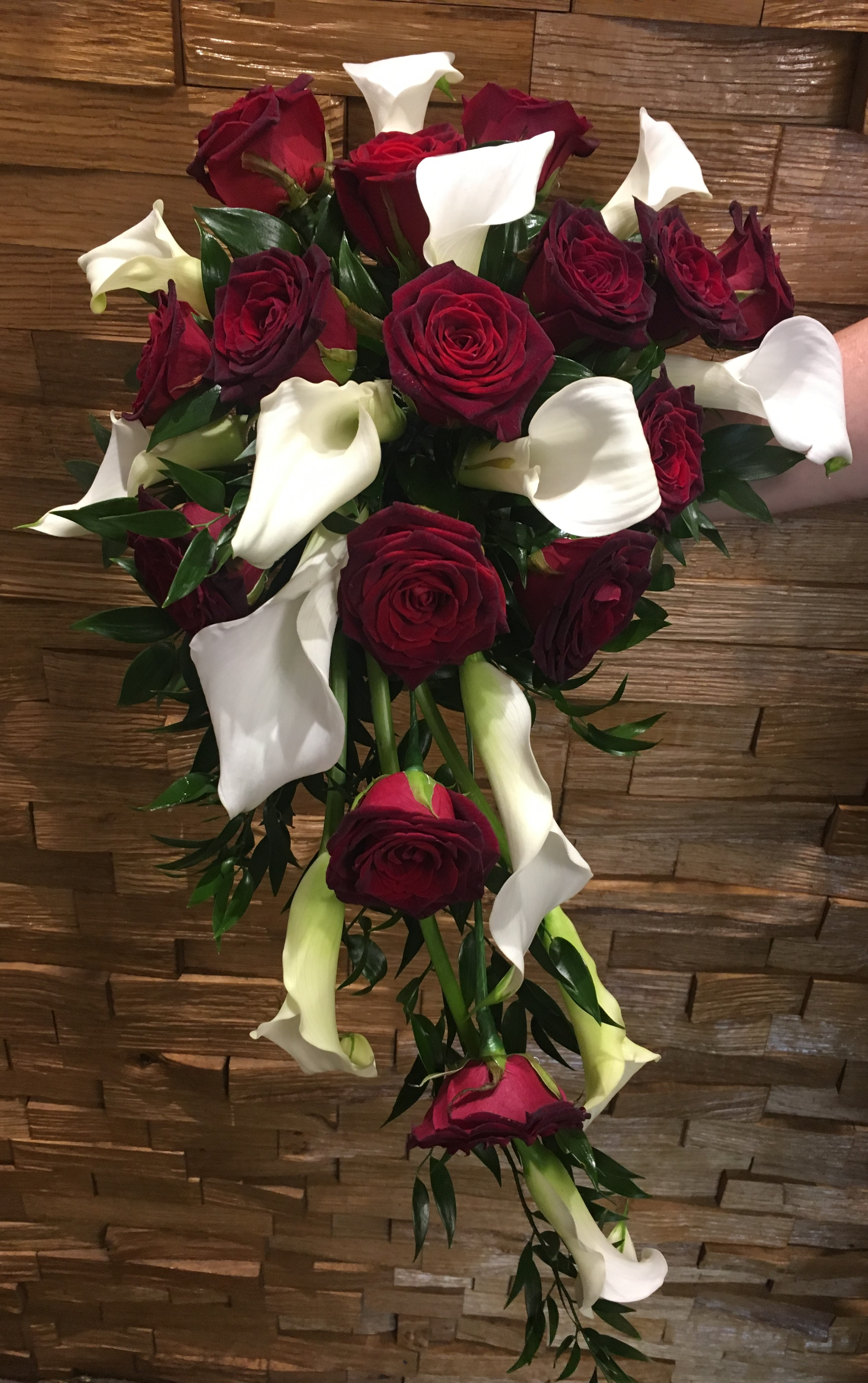 deep burgundy roses and calla in a shower bouquet wedding flowers