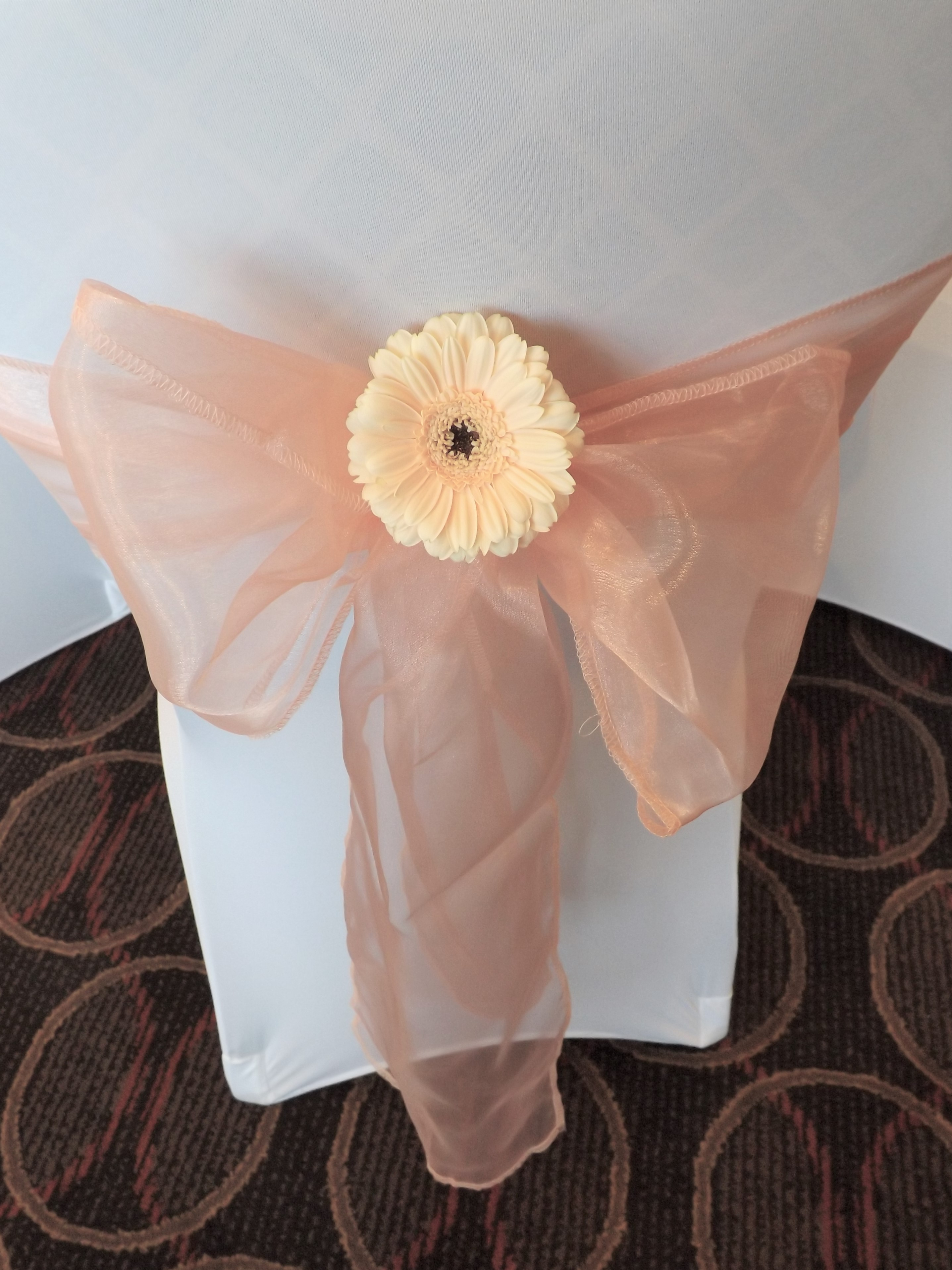 peach gerbera with peach chair sash