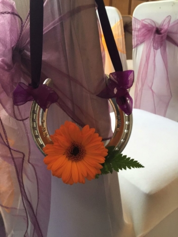 horse shoe in purple ribbons & orange gerbera